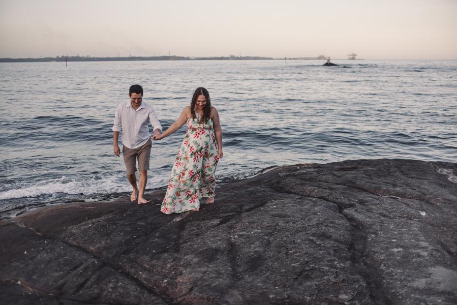 Casal andando sobre as pedras da Pousada do Farol. Vista do Mar de Vitória, Espírito Santo.