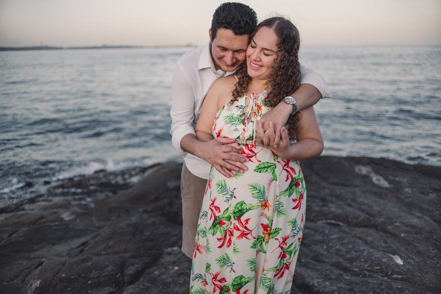 Casal gestante abraçados, sorrindo, com os olhos fechados.