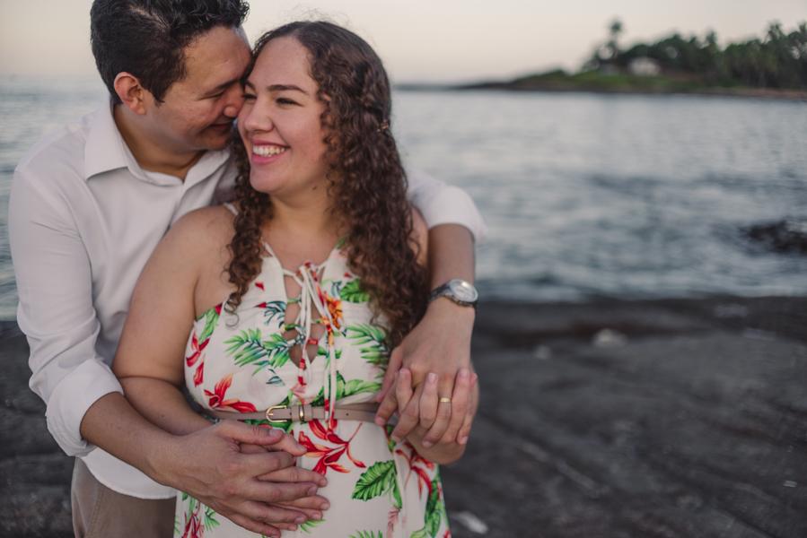 Casal sorrindo e abraçado na pedra da Pousada do Farol em Vila Velha. Morro do Moreno. Por do Sol.