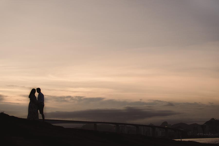 Silhueta do casal em por do sol na pedra da pousada do farol. Vista da terceira ponte de Vitória, ES.
