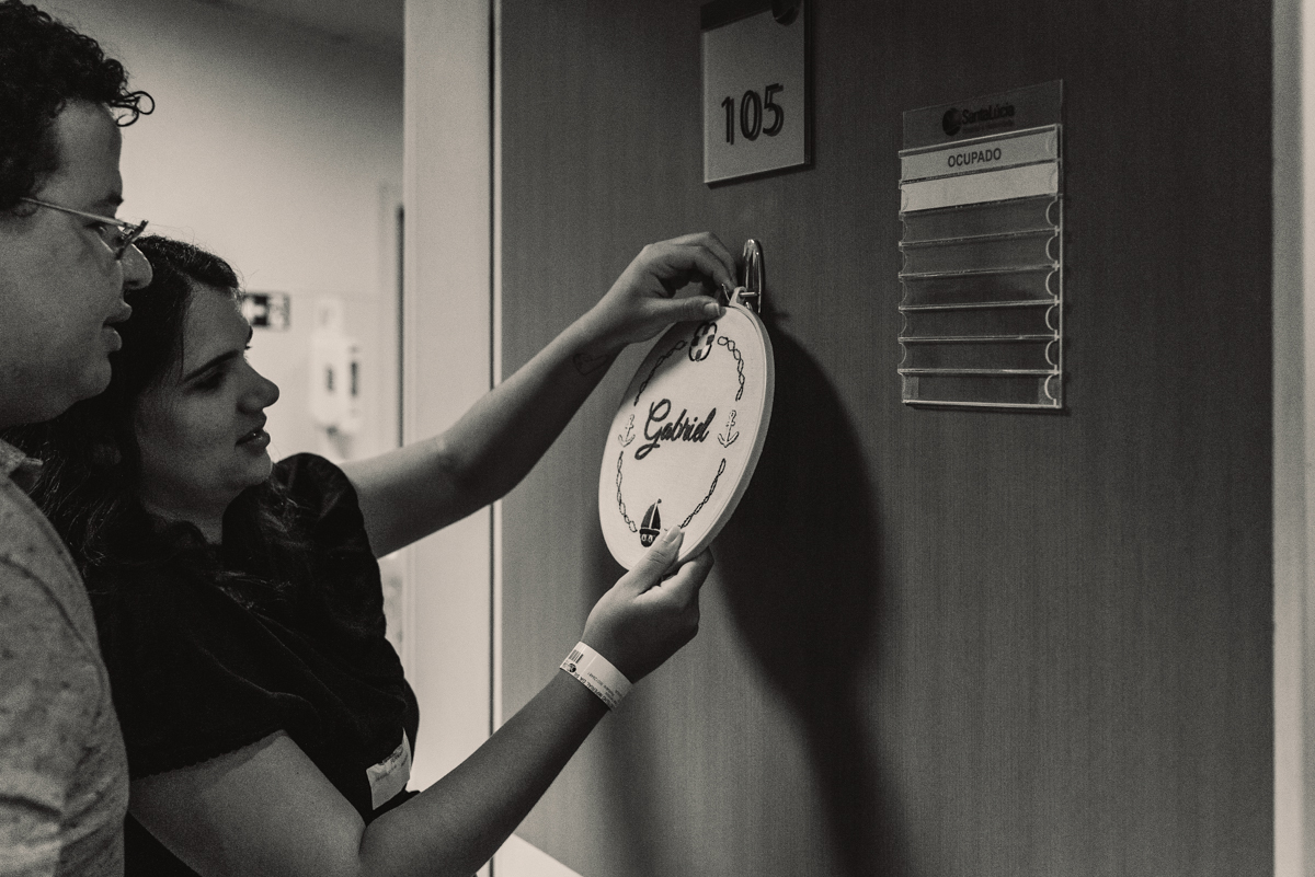 Casal colocando plaquinha na porta do quarto para receber o bebê após o parto. Plaquinha redonda pregada na porta