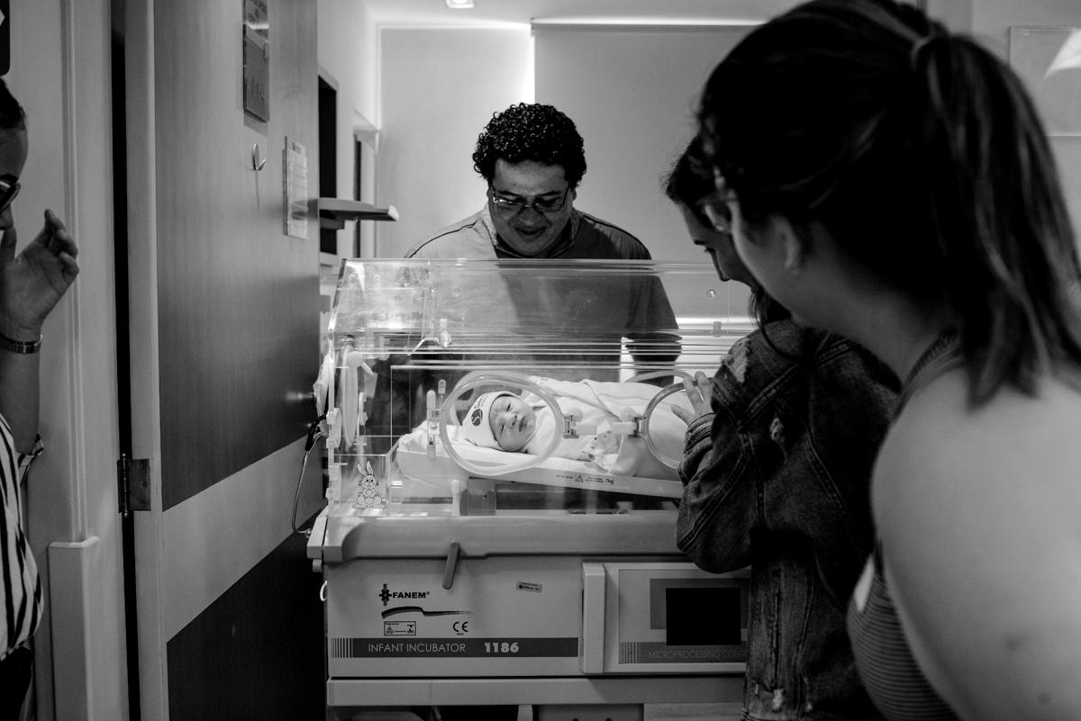 Família contemplando o bebê na sala da maternidade.