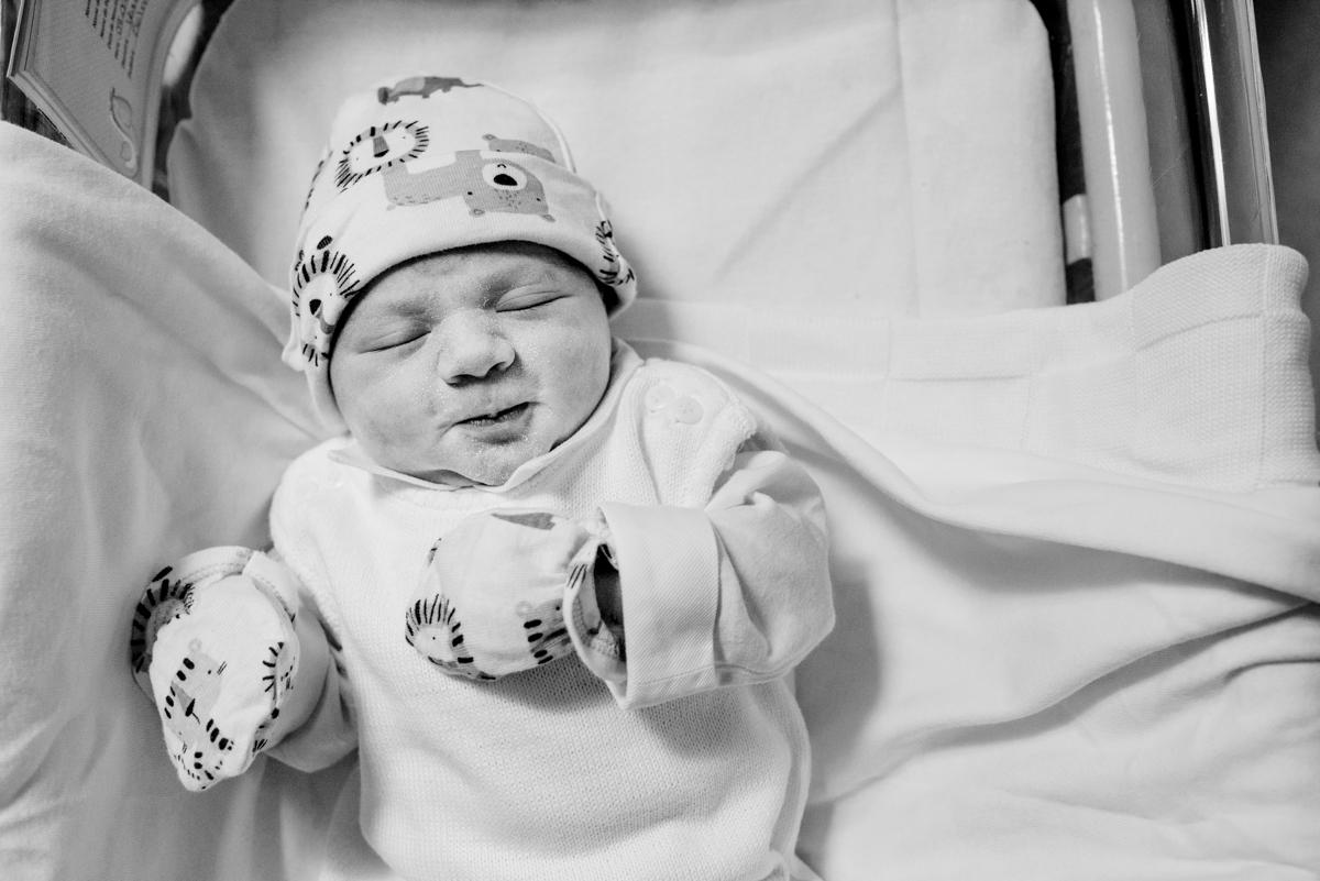 Bebê recém nascido de olhos fechados deitado no berço no quarto do hospital.