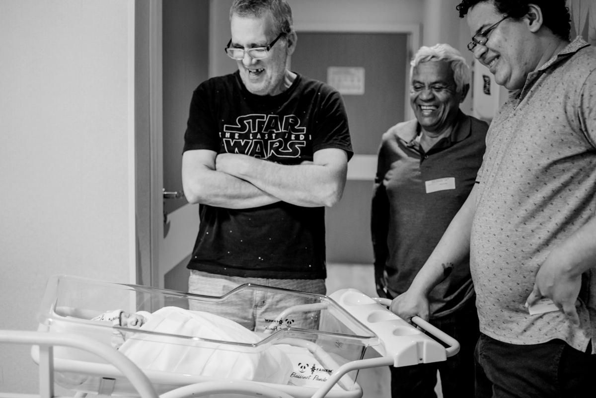 Filho, sogro e pai olhando o bebê no berço.