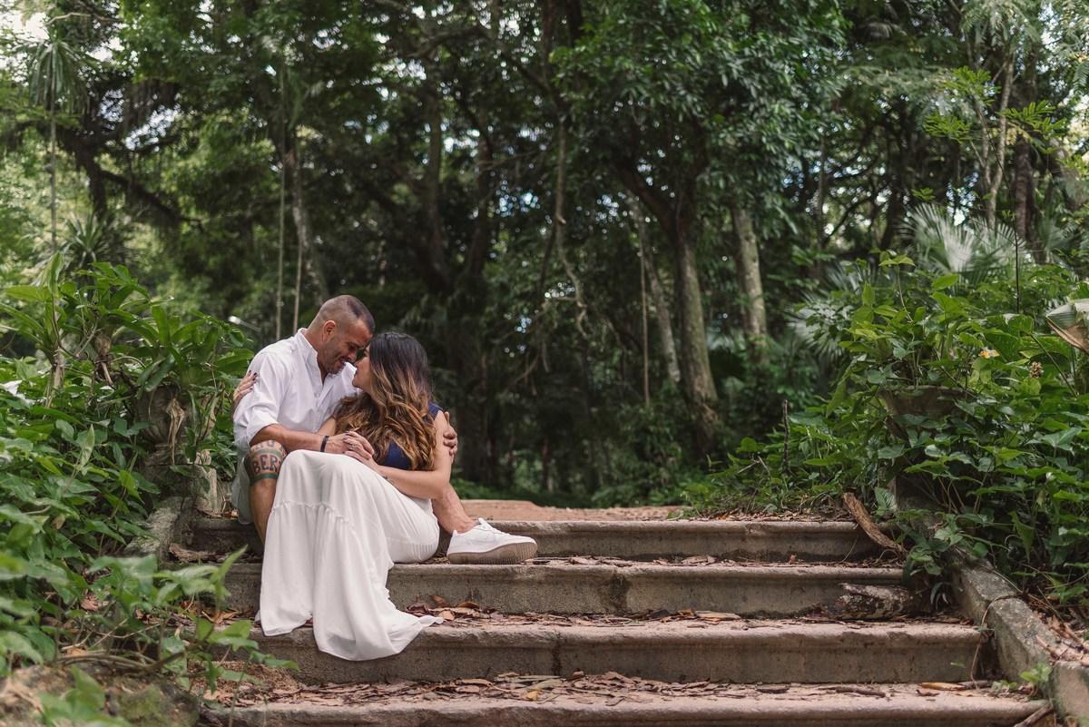 Casal sentando na escada do Parque Lage. Fotografia composta com vegetação do local. Casal está com testas coladas um ao outro.