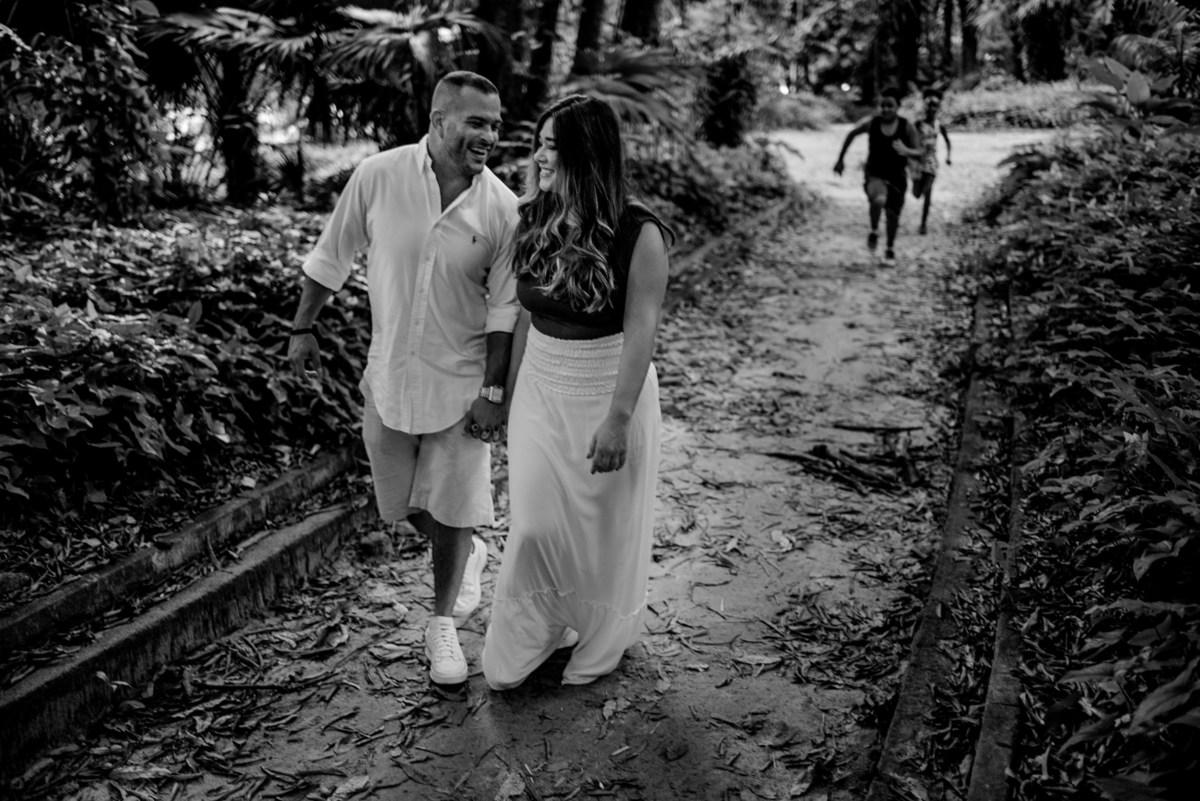 Casal andando sorrindo no parque Lage no Jardim Botânico no Rio de Janeiro. Crianças correndo atrás no corredor. Fotografia Preta e Branca.