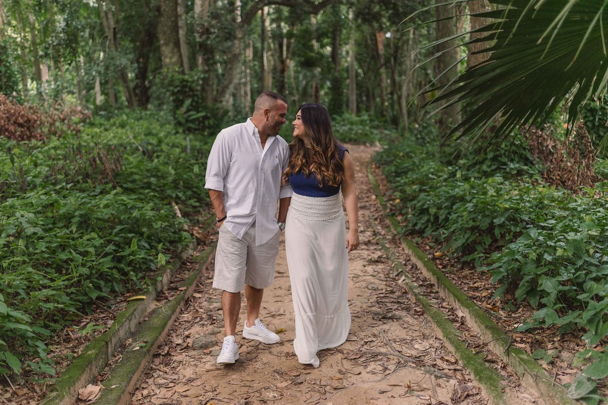 Ensaio Pré Casamento realizado no Parque Lage, no Rio de Janeiro. Casal andando e olhando um para o outro na rua de terra no parque.