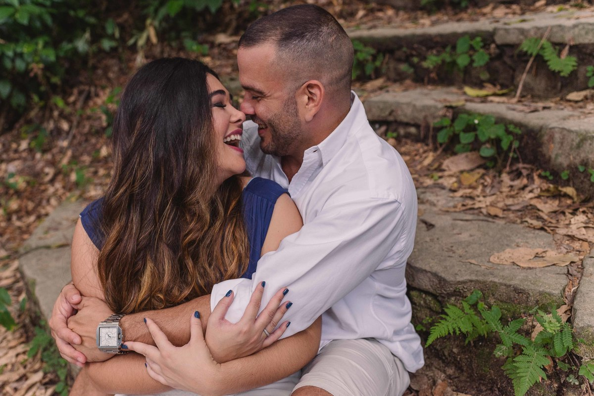 Casal sorrindo, sentados na escadaria do Parque Lage.