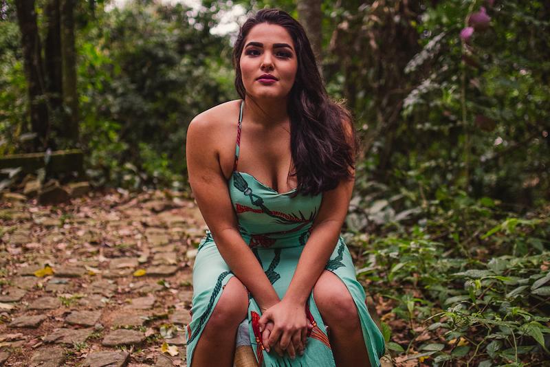 Modelo sentada no banco com olhar fixo. Ensaio fotográfico realizado no Parque da Fonte Grande.