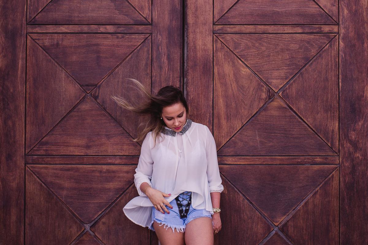 Fotografia do ensaio fotográfico pessoal, realizado na Ilha do Frade em Vitória - ES. Modelo em pé, olhando para baixo, com os cabelos ao vento em frente uma porta de madeira.