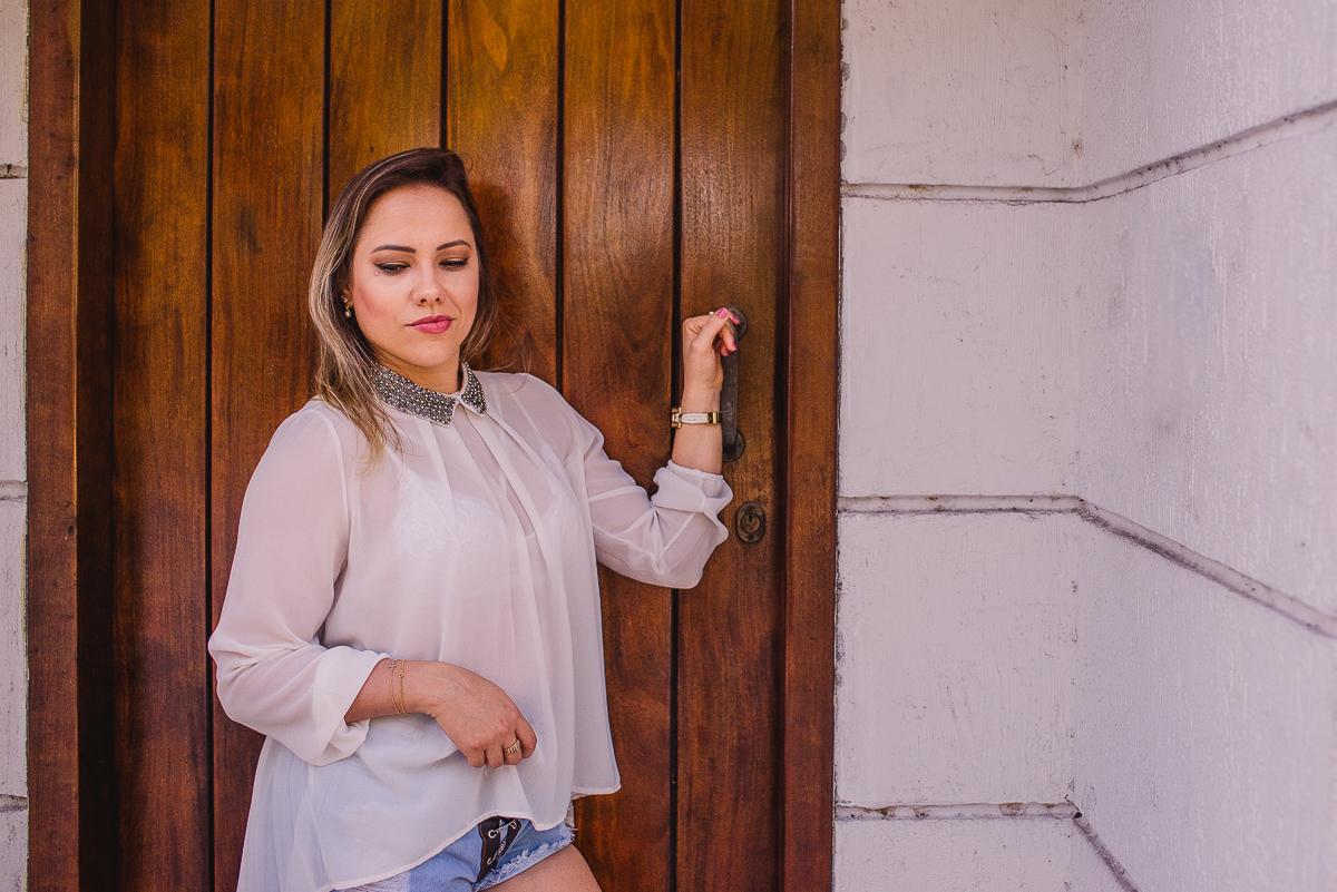 Ensaio fotográfico feminino. Modelo segurando a maçaneta da porta, com seu olhar voltado para baixo e com um leve sorriso no rosto.