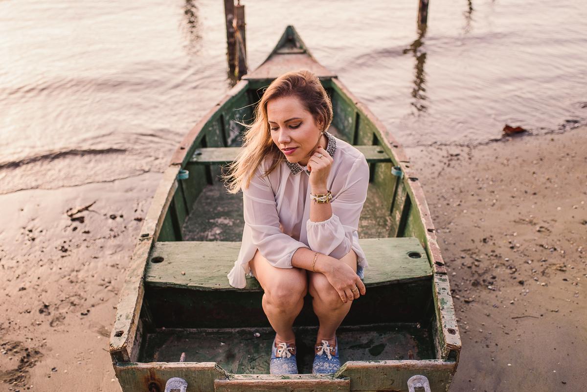 Modelo sentada num pequeno barco de madeira, atracado na Ilha do Frade, Vitória - ES. Ensaio Fotográfico Feminino.