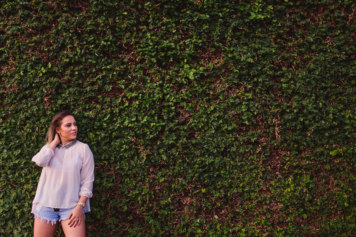 Modelo encostada no muro cheio de plantas trepadeiras.