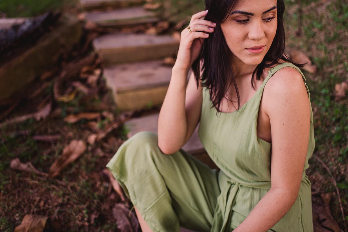 Fotografia feminina. Ensaio fotográfico. Modelo vestindo um macacão verde, de alcinha. Sentada na escadaria. Praia da Ilha do Frade. Vitória-ES.
