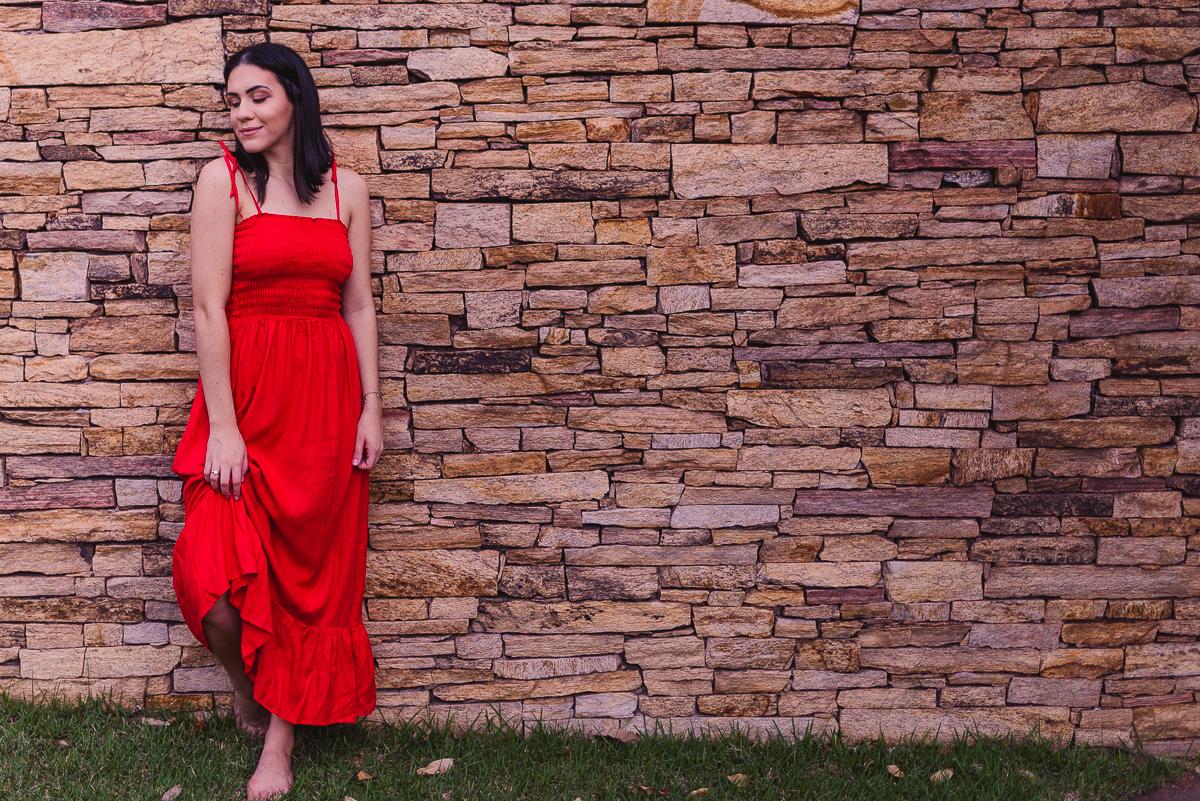 Fotografia feminina. Ensaio realizado na ilha do frade. Fotografia feita num muro de pedra. Modelo com pé apoiado na parede.
