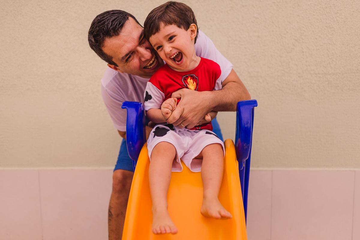Pai fazendo casquinha no filho. Fotografia de família em Vila Velha, ES - Itapuã.