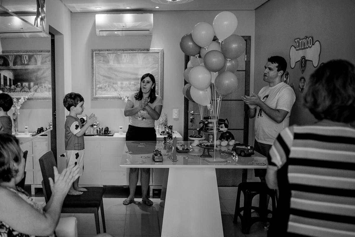 Fotografia preto e branco. Aniversariante na frente da mesa do bolo, cantando parabéns. Fotografia Documental de Família. Itapuã, Vila Velha - ES.