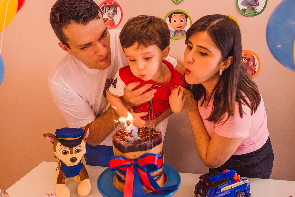 Momento de assoprar o bolo no aniversário infantil. Fotografia de Aniversário. Documental de família em casa.