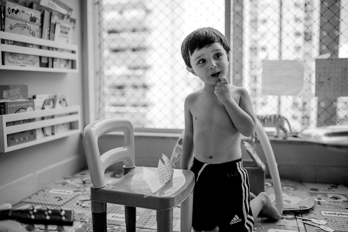 Aniversariante contando história dos 3 porquinhos para família. Fotografia Documental de Família. Aniversário Infantil em Itapuã, Vila Velha, ES.