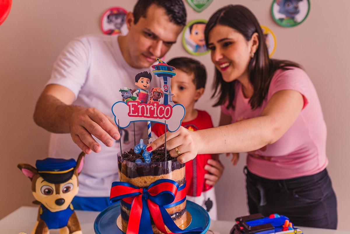Fotografia da família atrás da mesa de bolo. Preparando para cantar os parabéns para o filho de 3 anos.