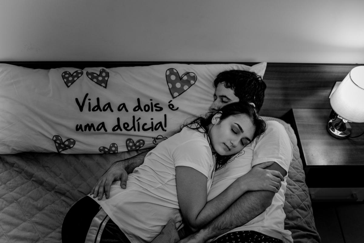 Fotografia - Ensaio de casal. Esposa deitada no peito do esposo. Este que está deitado com a cabeça sobre o travesseio que leva a frase: