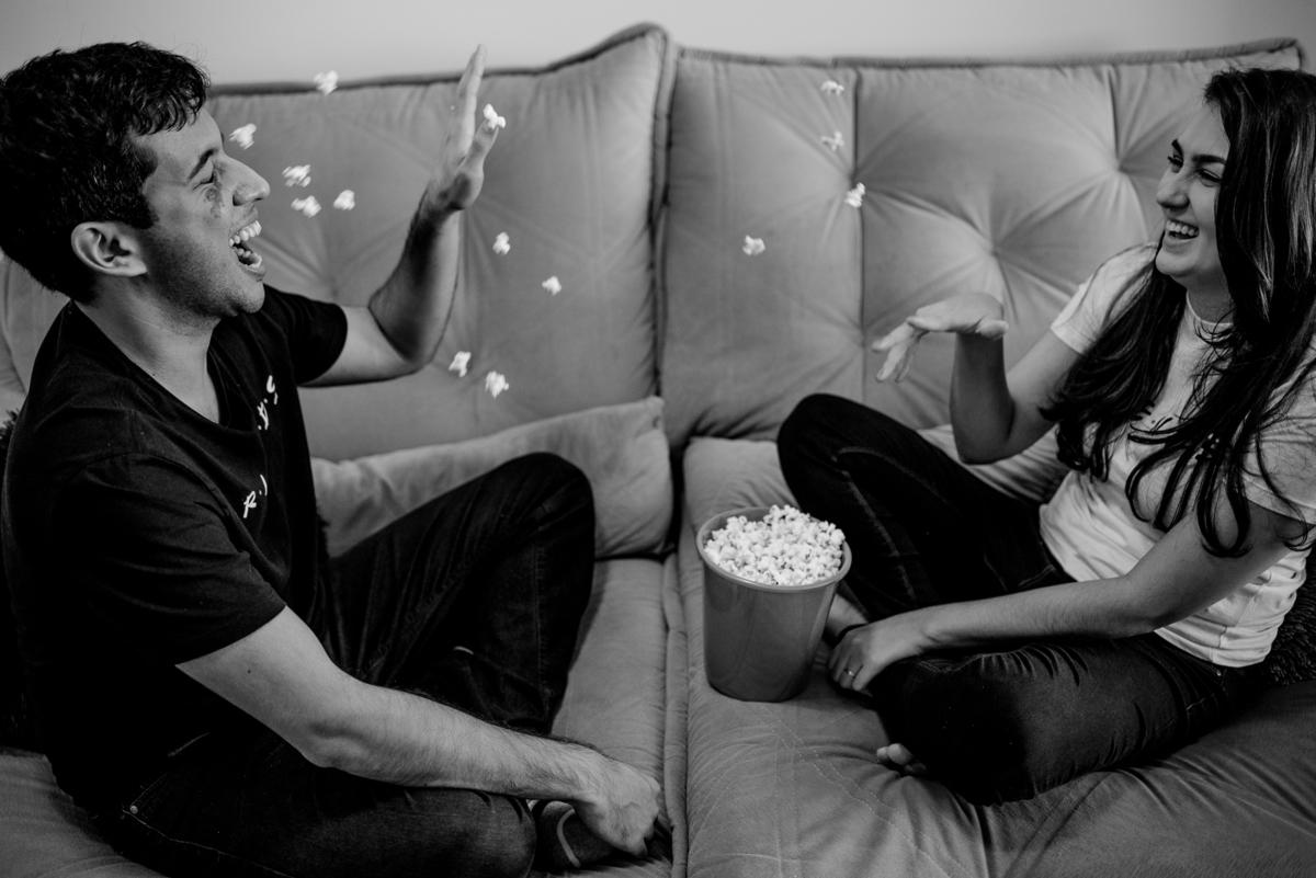 Fotografia preto e branco. Casal jogando pipoca um no outro.