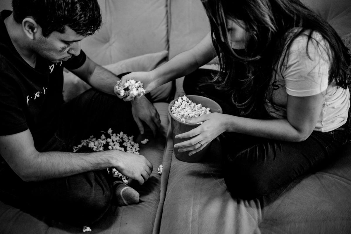 Fotografia de momento decisivo, onde as pipocas caíram no colo do esposo. Casal cantando as pipocas que caíram no sofá. Ensaio fotográfico realizado em casa. Enseada do Suá - Vitória - ES