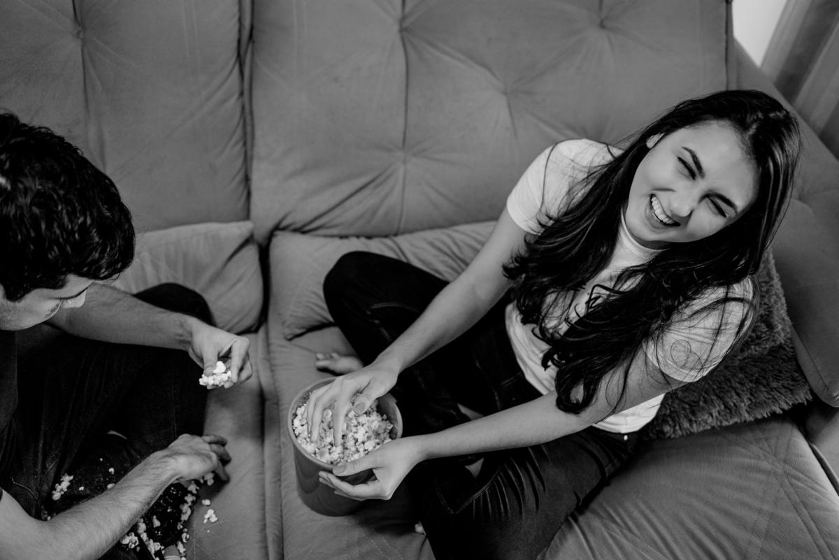 Esposa rindo do esposo catando as pipocas que caíram no sofá. Ensaio fotográfico em casa. Enseada do Suá - Vitória - ES.