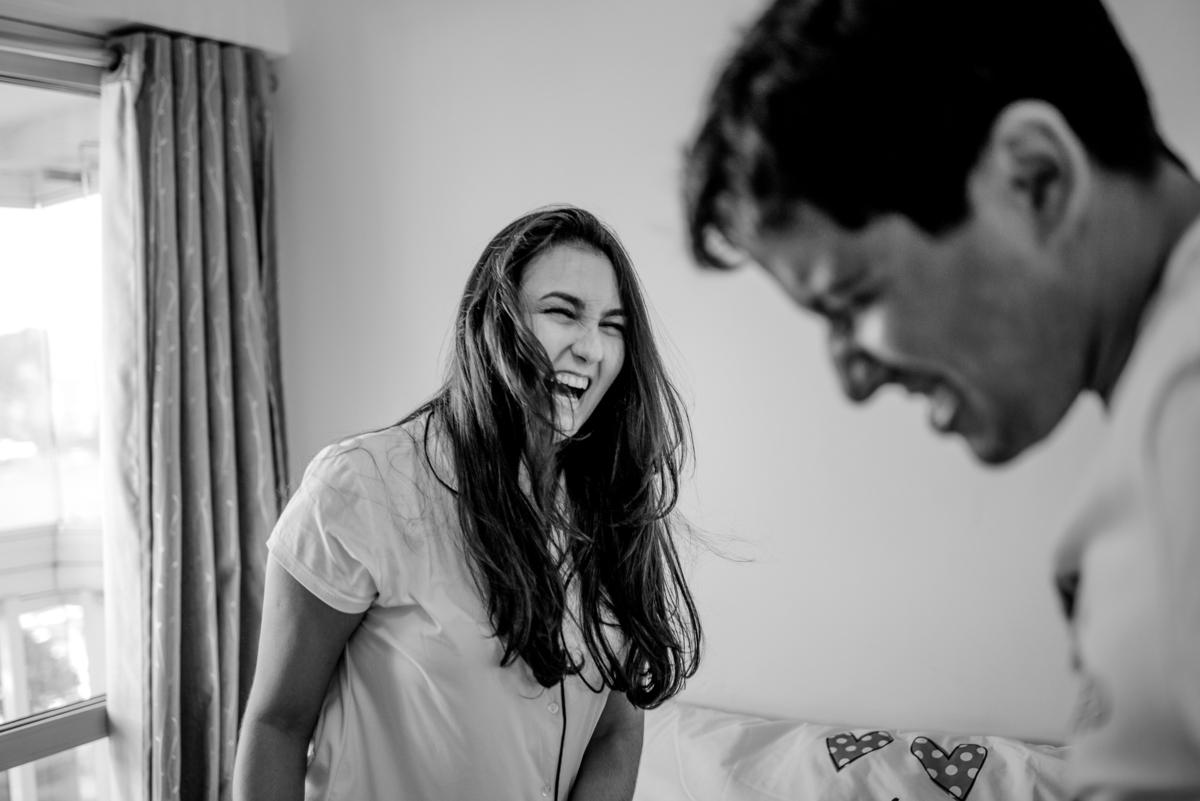 Esposa rindo do esposo. Fotografia de casal. Ensaio realizado em casa.
