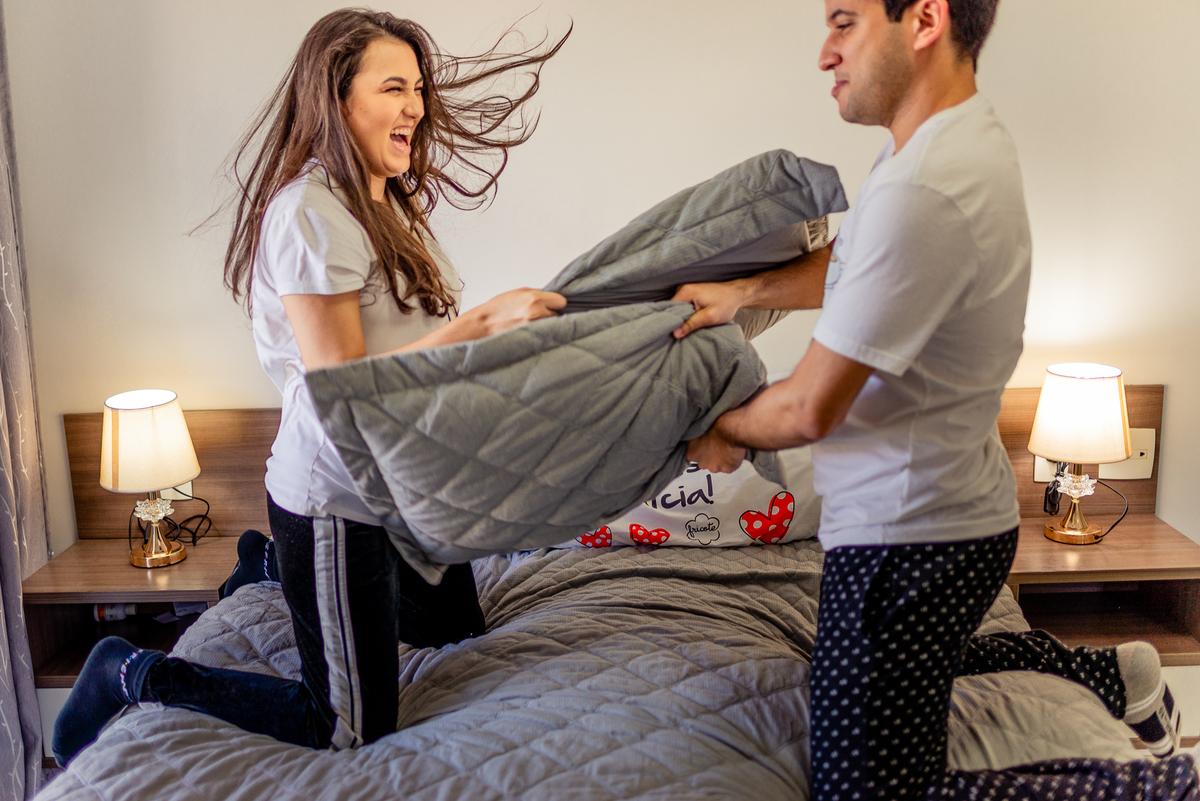 Fotografia retrata guerrinha de travesseiros entre o casal, ajoelhados na cama.  Ensaio fotográfico em casa - Enseada do Suá - Vitória - ES