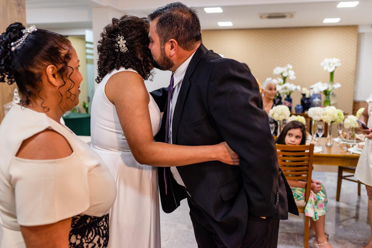 Noivo abraçando a noiva ao recebê-la no altar.