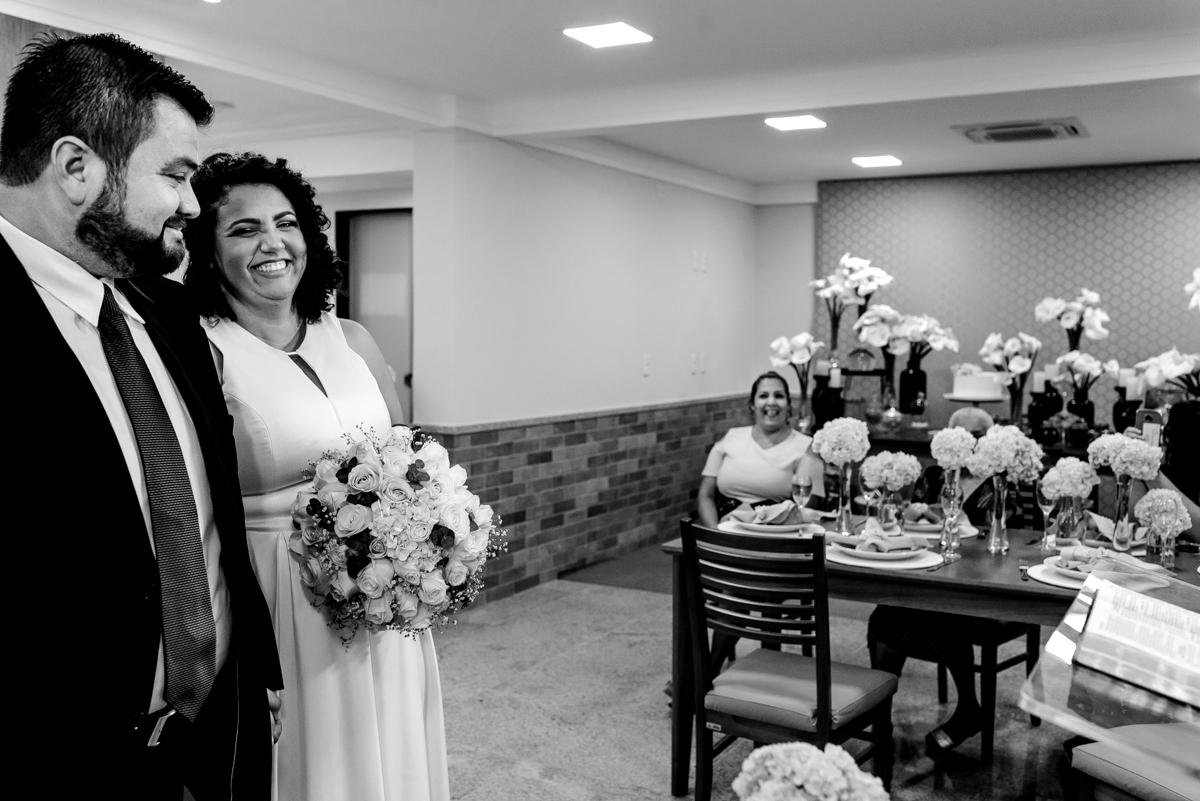 Noivo olhando para sogra que está sentada próxima ao altar. Fotografia de casamento
