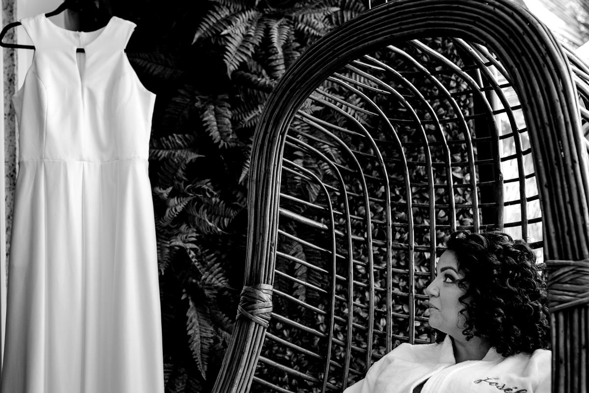 Noiva sentada olhando para o vestido de noiva - Fotografia de Casamento - Making Of Casamento - Vitória ES