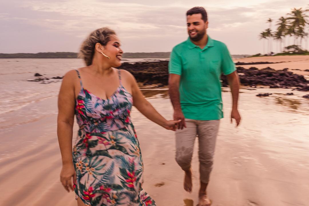 Ensaio fotográfico pré casamento. Casal caminhando na areia da praia de coqueiral de aracruz, espírito santo