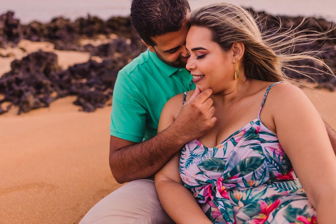 Casal sentado na areia da praia de coqueiral de aracruz