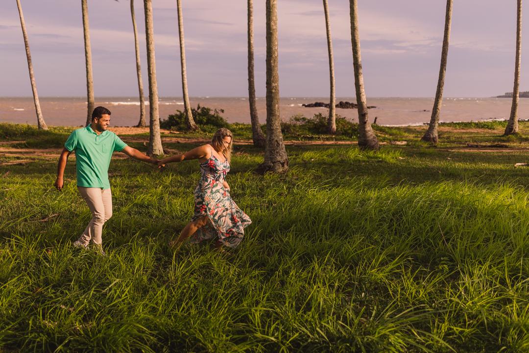 Casal caminhando sobre o gramado entre os coqueiros na praia de coqueiral de aracruz no espírito santo.