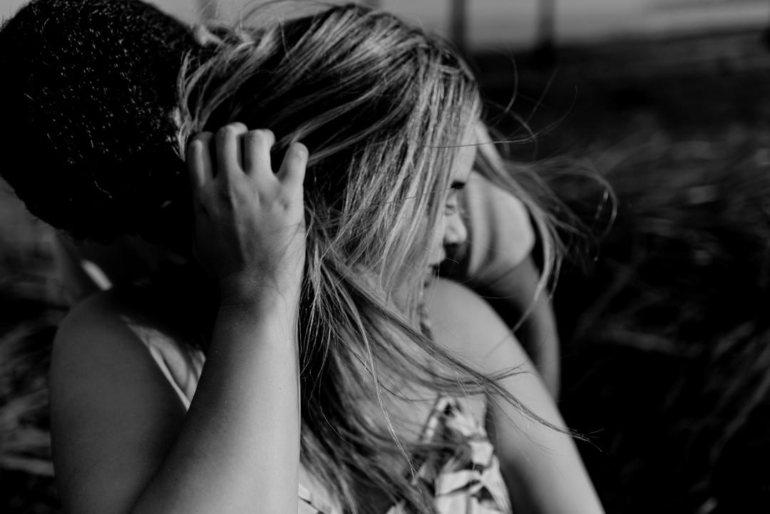 Foto Preto e branco. Mulher com a mão no cabelo e vendo assoprando. Ensaio Pré Casamento em Coqueiral de Aracruz