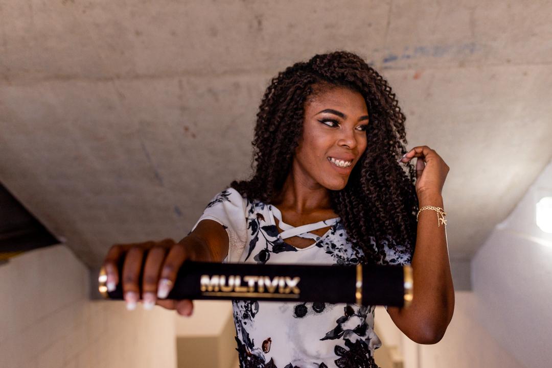 Formanda segurando o canudo de formatura multivix, olhando para o lado e passando a mão no cabelo