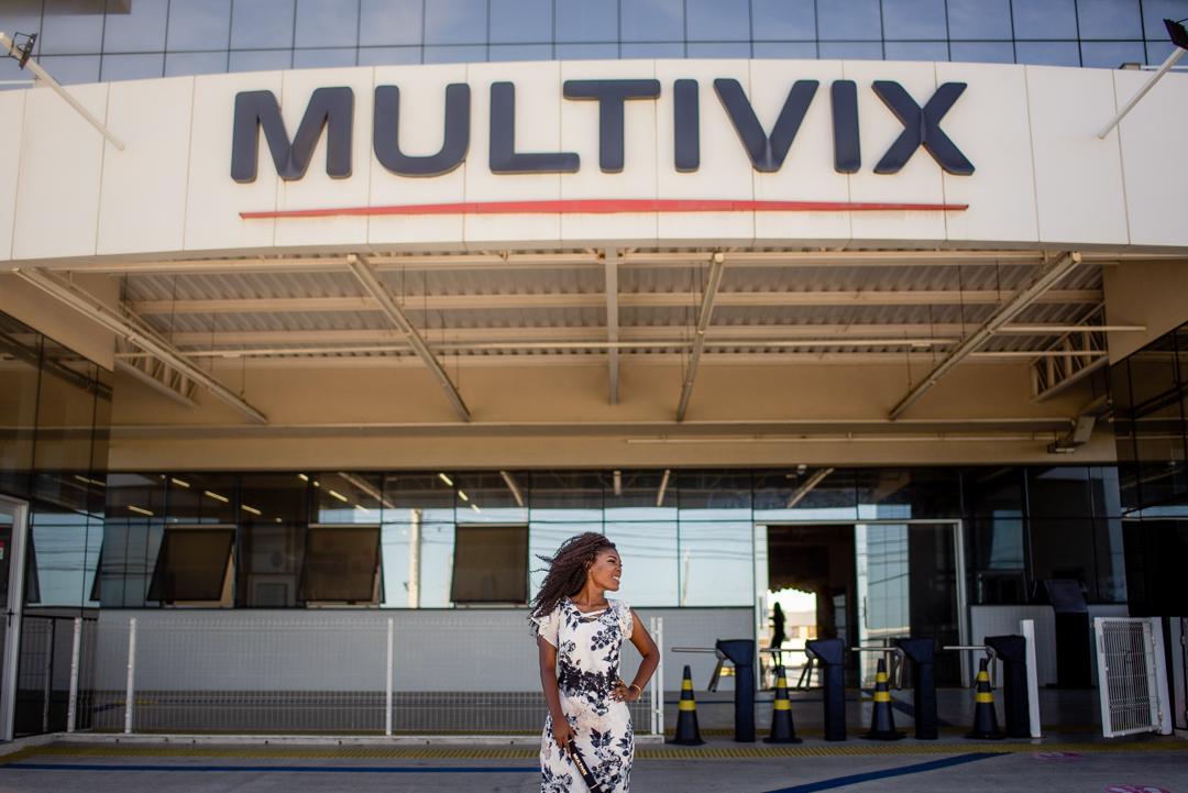 Formanda posando para foto na fachada da faculdade multivix.
