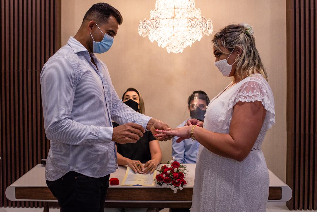 Fotografia realizado no momento em que os noivos estao trocando alianças no cartório. casamento no cartório