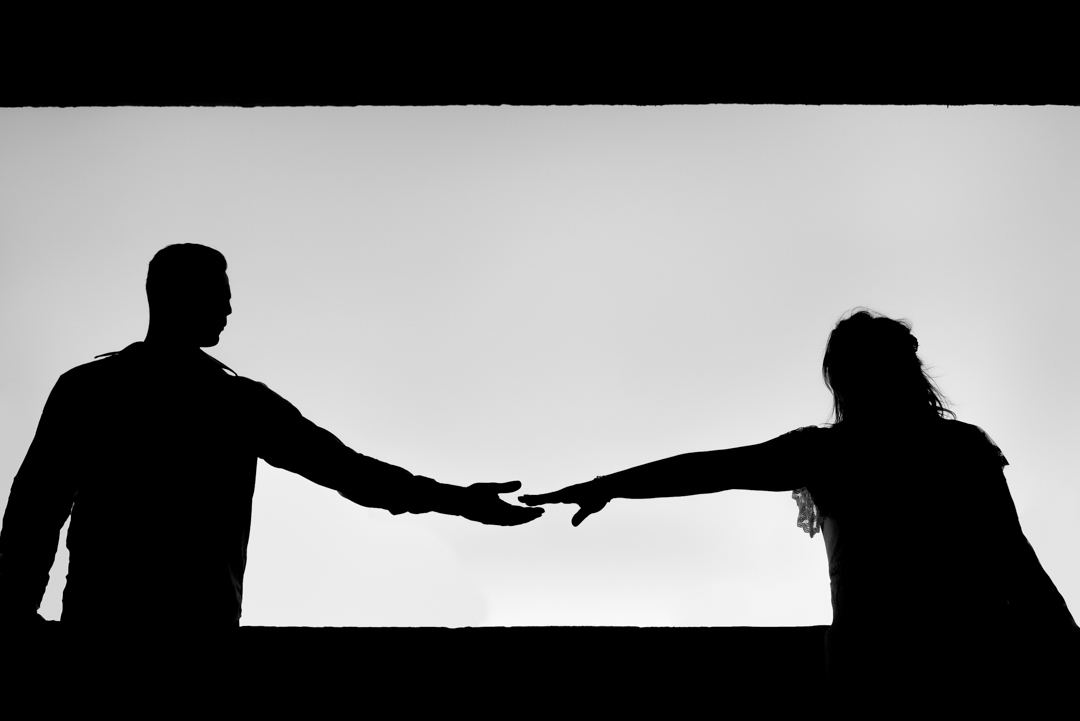 Fotografia preto e branco em silhueta do casal dando as maos.