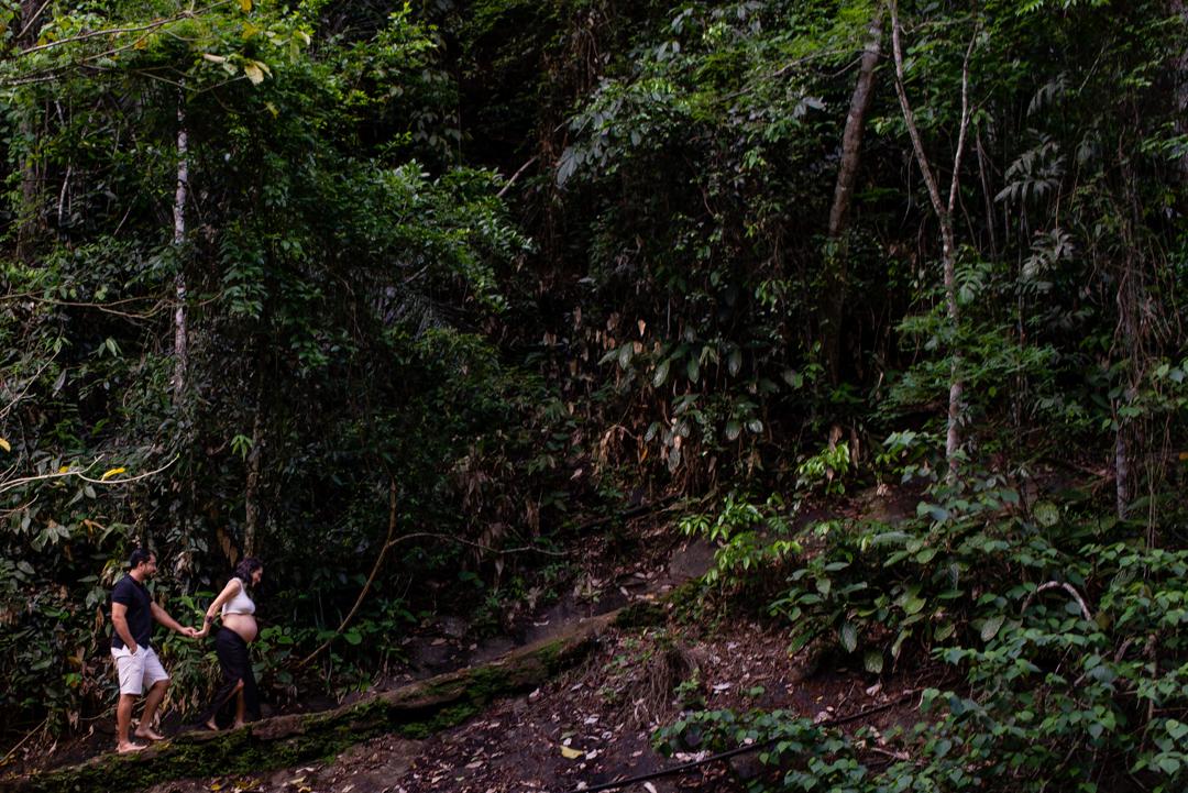 Ensaio Fotográfico realizado na cachoeira do Aloísio em Viana, Espírito Santo. Casal da foto está subindo uma estrada de pedras e ao fundo rochas cheias de arvores compondo a vegetação.