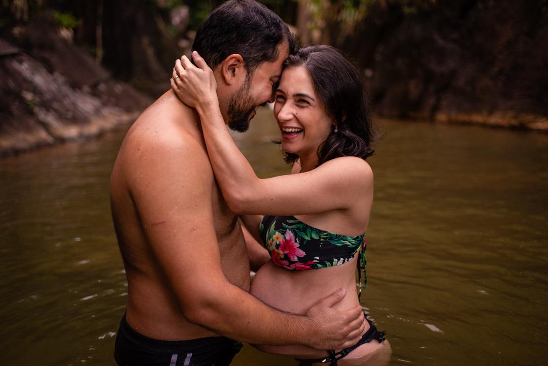 Fotografia da gestante na cachoeira sorrindo junto com seu esposo. Eles estão abraçados. Retrato foi feio no momento em que ela está gargalhando junto com ele.