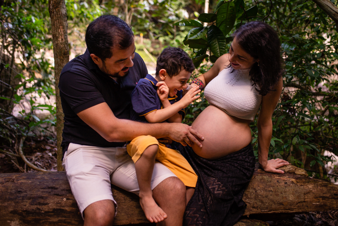 Fotografia da família brincando com a barriga da gestante e fazendo cócegas no filho mais velho. Ensaio fotográfico em Viana, ES. Cachoeira