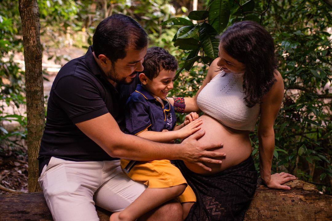 Fotografia da familia olhando para barriga da mãe gravida.