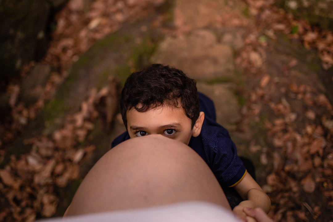 fotografia de ensaio de gestante. filho mais velho se escondendo embaixo da barriga da mãe gravida.