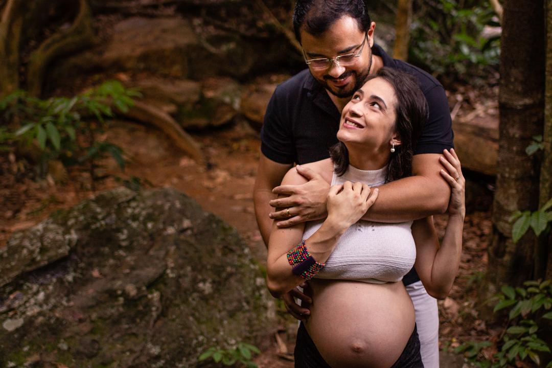 Fotografia de ensaio de gestante. Esposa olhando para esposo. Ele está abraçado por detrás dela e ela sorrindo para ele.
