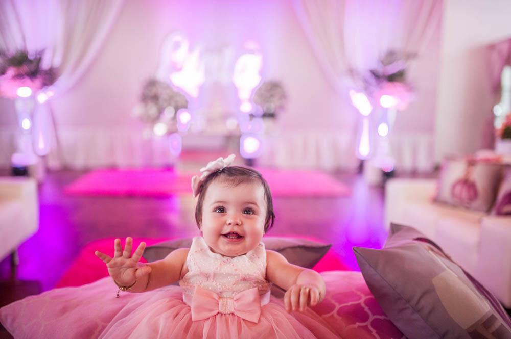 menina de um ano sentada com as mãos para cima sorrindo