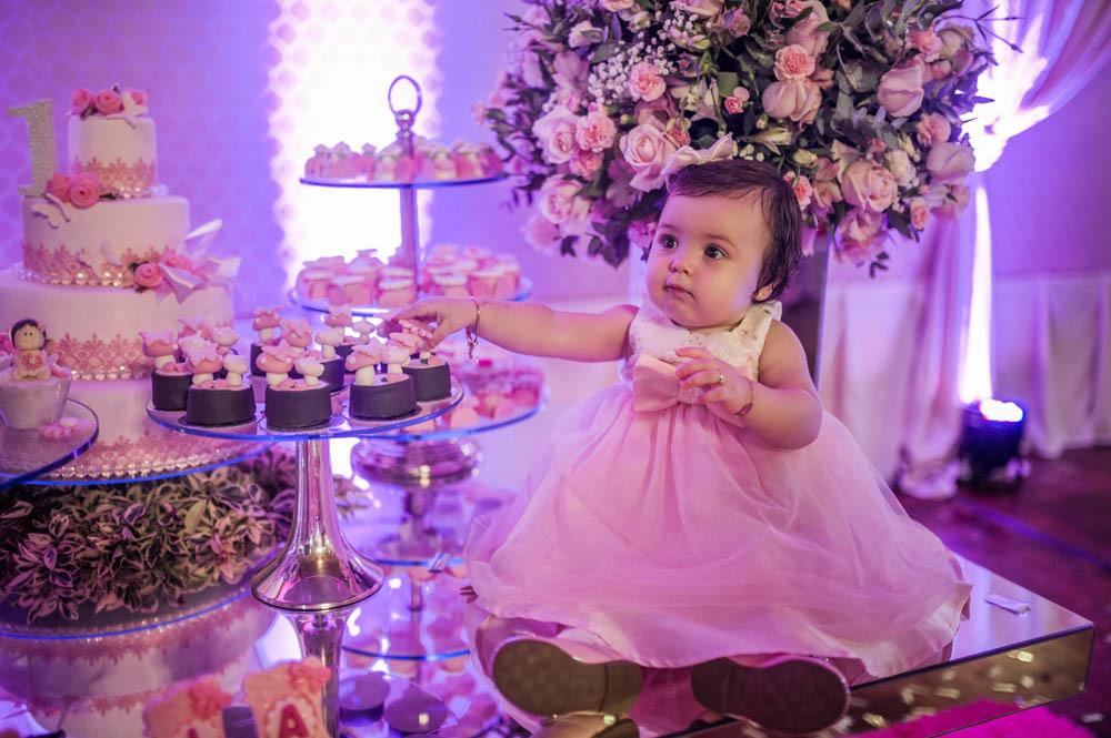 bebê menina sentada em cima da mesa de doces tentando pegar um doce