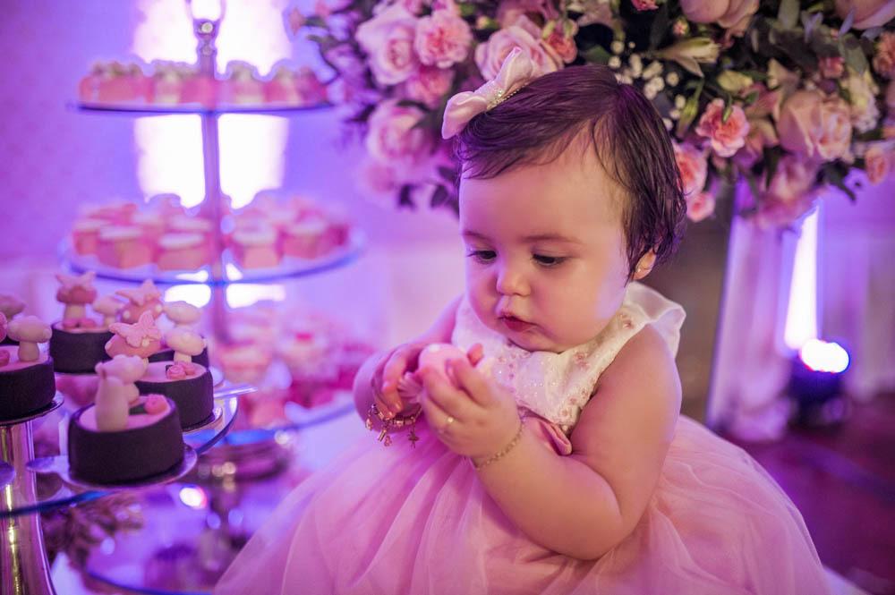 bebê menina sentada comendo um doce vestida de rosa